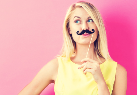 young people fun: Young woman holding paper party sticks on a pink background
