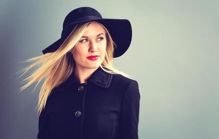 mujer elegante: Joven y bella mujer rubia en un abrigo negro