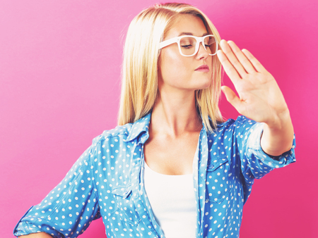 Young woman making a rejection pose on a pink background