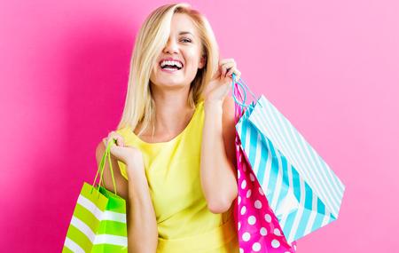 Gelukkige jonge vrouw die boodschappentassen op een roze achtergrond houdt