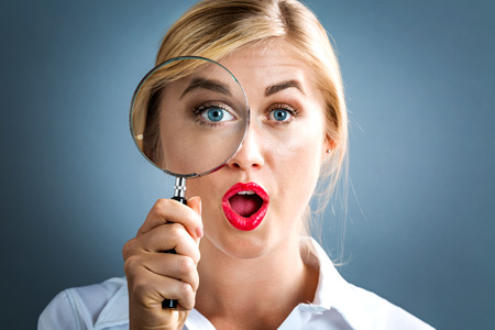 Young woman looking through a magnifying glass