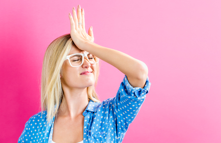 Young woman making a mistake on a pink background Stockfoto