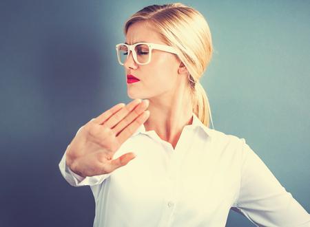 De jonge vrouw die een afwijzing vormt stelt op een grijze achtergrond Stockfoto - 70423905