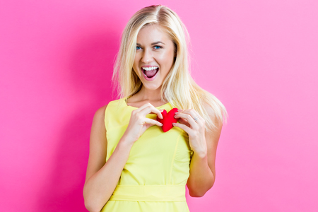 Happy young woman holding a heart cushion on a pink background