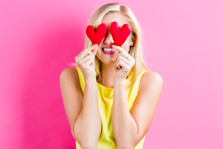 blonde females: Happy young woman holding heart cushions on a pink background