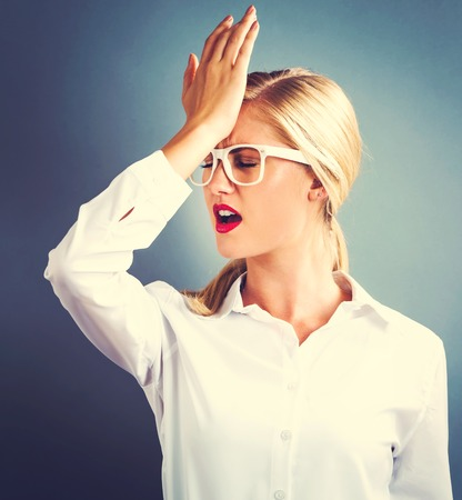 Young woman making a mistake on a gray background