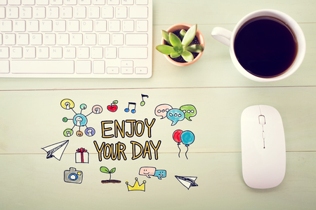 desk light: Enjoy Your Day concept with workstation on a light green wooden desk Stock Photo