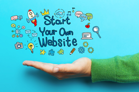 Start Your Own Website concept with hand on blue background Stock Photo