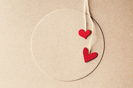 paper craft: Handmade small paper hearts with strings on earthy colored paper background