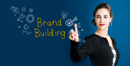 Brand Building concept with business woman on a dark blue background 版權商用圖片