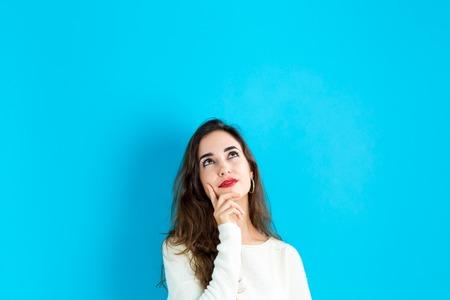 personas pensando: Mujer joven en una pose reflexiva sobre un fondo azul