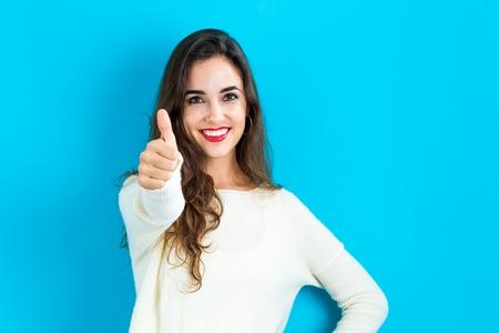 Gelukkige jonge vrouw die een duim omhoog op een blauwe achtergrond