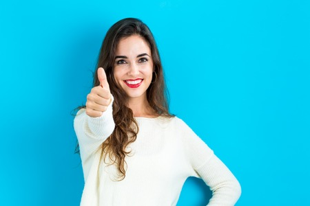 alegria: mujer joven feliz dando un pulgar hacia arriba sobre un fondo azul Foto de archivo