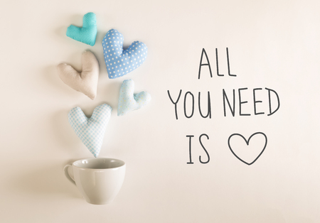 All You Need Is Love message with blue heart cushions coming out of a coffee cup Stock Photo