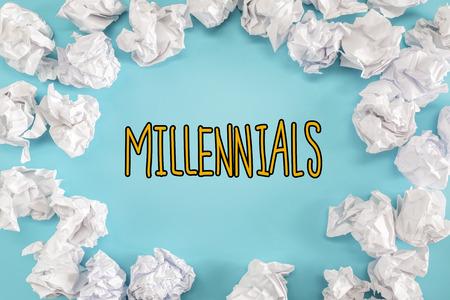 Millennials text with crumpled paper balls on a blue background