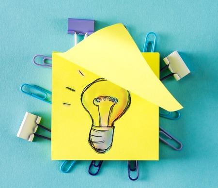 Light Bulb on a sticky note on a blue background