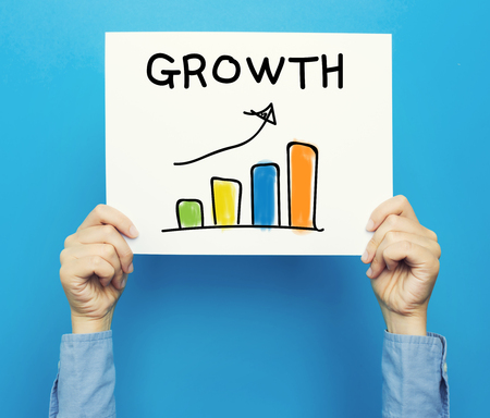 hand holding paper: Growth Graph on white poster on a blue background Stock Photo