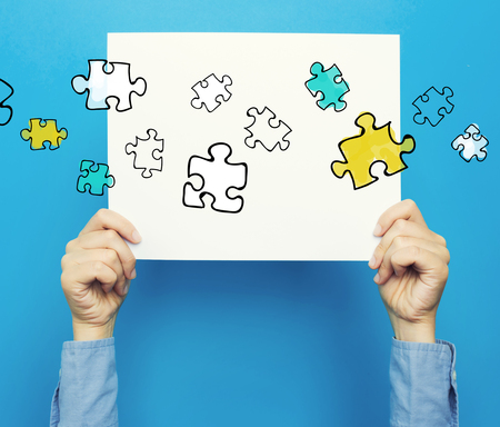 hand holding paper: Puzzles on white poster on a blue background