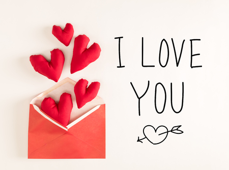 I Love You message with red heart cushions coming out of an envelope