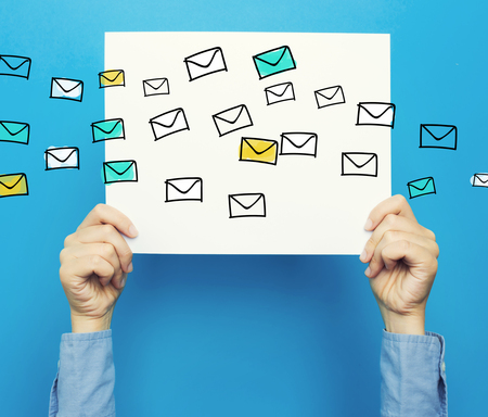 hand holding paper: Emails on white poster on a blue background