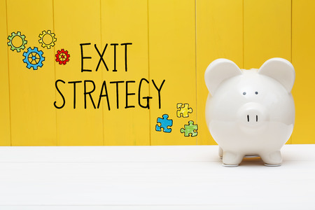 Exit Strategy text with piggy bank over yellow wall Stock Photo