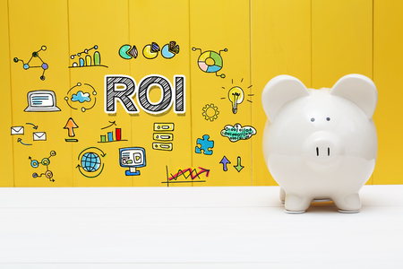 ROI text with piggy bank over yellow wall Stock Photo