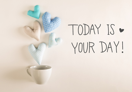 Today Is Your Day message with blue heart cushions coming out of a coffee cup Фото со стока