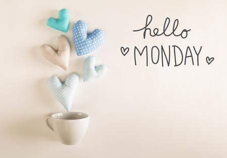 Hallo maandagbericht met blauwe hartkussens die uit een koffiekop komen Stockfoto