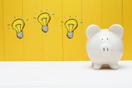 Light Bulbs with piggy bank over yellow wall Stock Photo