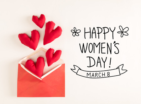 Womens Day message with red heart cushions coming out of an envelope