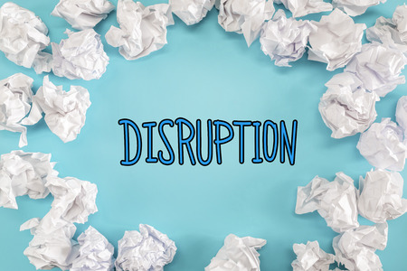 disrupting: Disruption text with crumpled paper balls on a blue background