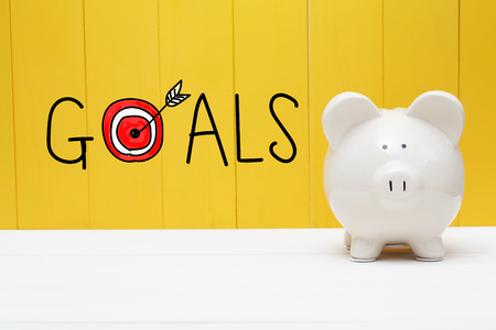 Goals text with piggy bank over yellow wall Stock Photo