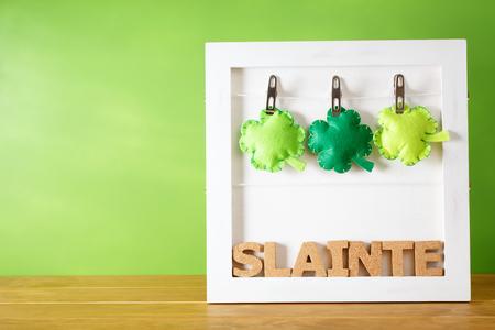 17th: Saint Patricks Day Slainte message with clover cushions Stock Photo