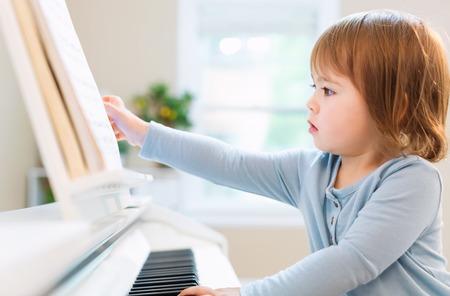 pianista: Muchacha del niño que juega el piano en su casa