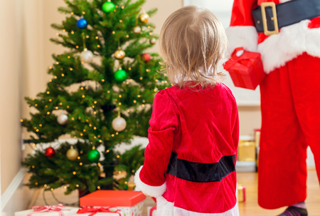 Toddler girl interacting with Santa Claus by the Christmas tree