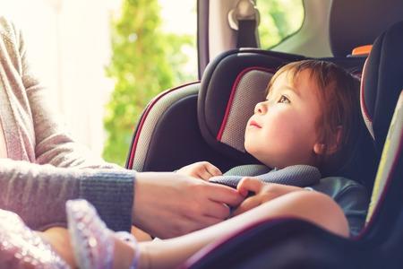Muchacha del niño abrochado en el asiento del coche Foto de archivo - 73897173