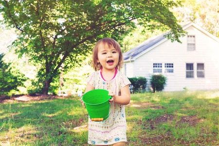 Happy toddler girl playing with watering cans and buckets outside Stock Photo