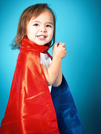 Happy toddler girl playing in a super hero cape Stock Photo