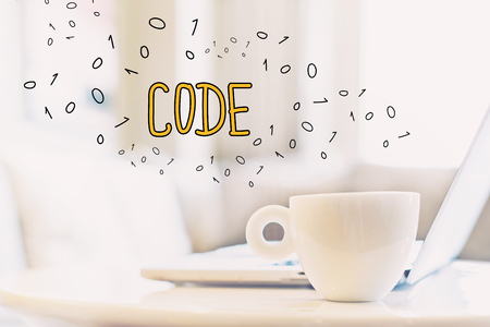 Code concept with a cup of coffee and a laptop