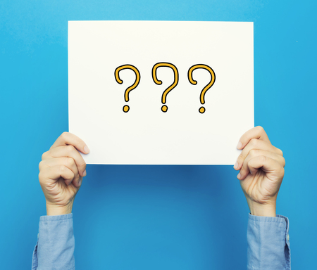 hands holding sign: Question Mark text on a white poster on a blue background
