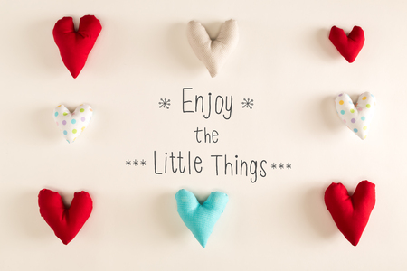 multiple objects: Enjoy The Little Things message with blue heart cushions on a white paper background