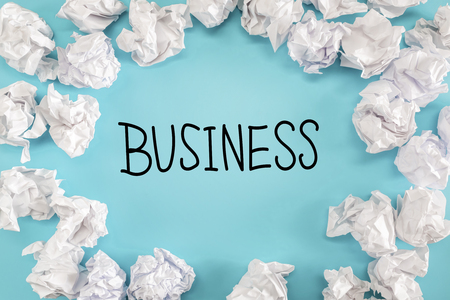 scrunch: Business text with crumpled paper balls on a blue background