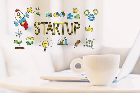 Start Up concept with a cup of coffee and a laptop Stock Photo