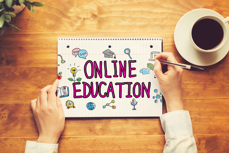 Online Education text with a person holding a pen on a wooden desk