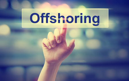 offshoring: Offshoring concept with hand pressing a button