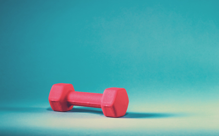 Pink dumbbell on a blue gradient background