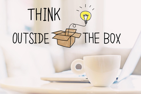 Think Outside The Box concept with a cup of coffee and a laptop