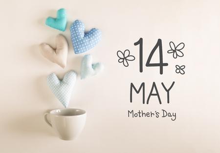 Mensaje de Día de la Madre con cojines azules del corazón que sale de una taza de café Foto de archivo - 74615096