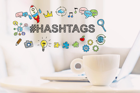 Hashtags concept with a cup of coffee and a laptop Banco de Imagens