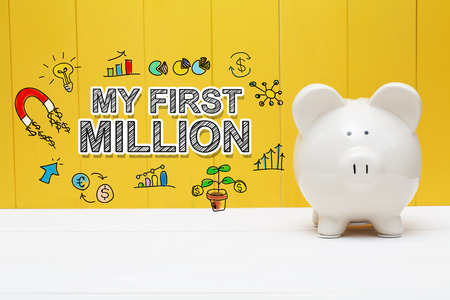My First Million text with piggy bank over yellow wall Stock Photo